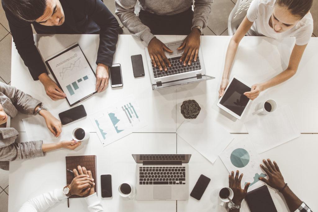 Microsoft 365 for Business Menschen sitzen am Tisch und arbeiten am Laptop